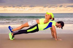 זוג עושה על החוף שכיבות סמיכה