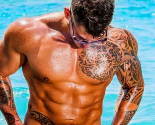 בחור מקועקע עם גוף שרירי בבריכה