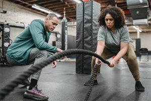 אישה מתאמנת עם חבלים ליד המאמן שלה