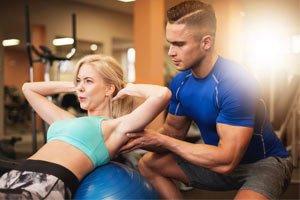 מאמן עוזר ללקוחה בתרגיל בטן