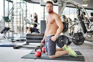 אדם שרירי בלי חולצה עושה אימון קטלבלס