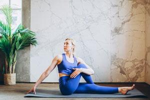 אישה עושה מתיחות על מזרן יוגה