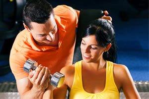 מאמן עוזר ללקוחה שלו עם המשקולת