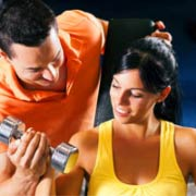 מאמן כושר עוזר ללקוחה שלו עם המשקולת