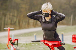אישה עם מסיכה עושה ספורט