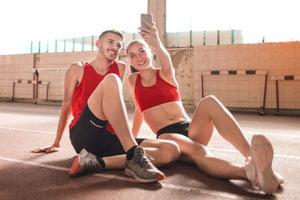זוג ספורטיבי עושה סלפי במכון כושר
